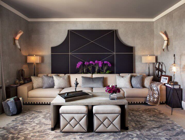 ottoman-coffee-table-with-decorative-pillows-on-the-sofa-and-horn-sconces-on-the-wall-also-headboard-behind-long-sofa-instead-of-art-with-orchid-flower-and-gray-walls-for-living-room-915x693-718x543